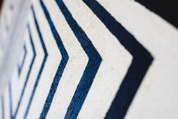 As linhas gostam de setas pretas no fundo branco pintado em uma parede que indica o sentido.