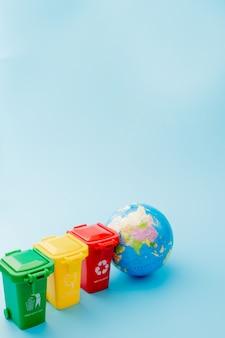 As lixeiras amarelas, verdes e vermelhas com reciclam o símbolo no fundo azul. mantenha a cidade arrumada. deixa o símbolo de reciclagem. conceito de proteção da natureza