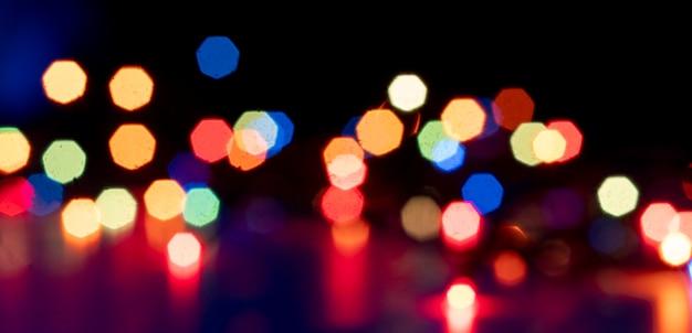 As luzes coloridas abstratas do bokeh da guirlanda na celebração da festa, banner largo