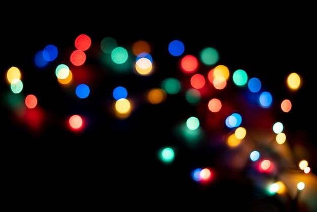 As luzes coloridas abstratas do bokeh da guirlanda na celebração da festa