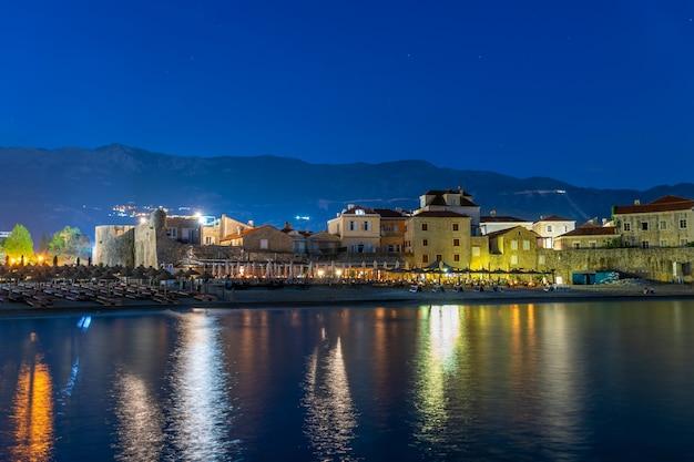 As luzes da cidade da noite são refletidas nas águas costeiras.
