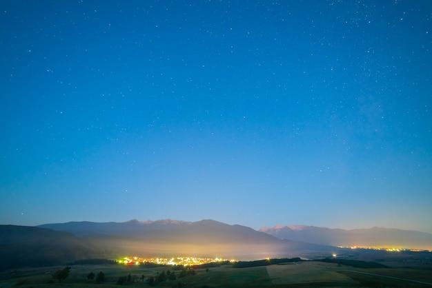 As luzes da cidade pitoresca no fundo do céu estrelado. noite noite