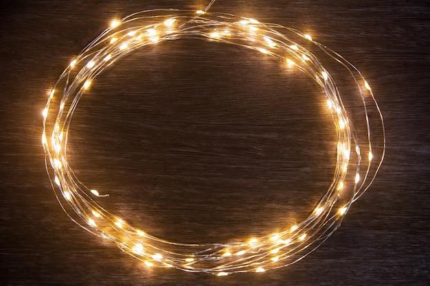 As luzes de natal moldam a decoração na madeira escura com espaço da cópia.