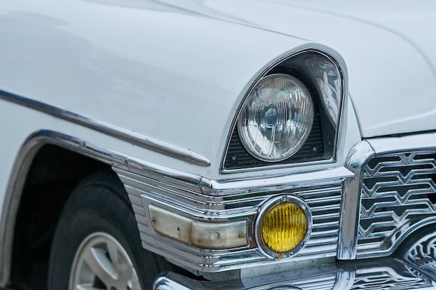 As luzes dianteiras de um velho carro branco para qualquer finalidade