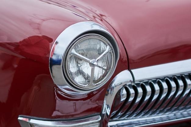As luzes dianteiras de um velho carro vermelho