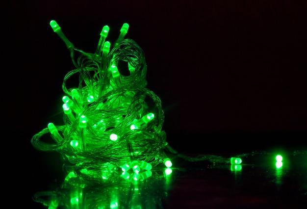 As luzes são verdes no formato de uma árvore de natal em um fundo escuro.
