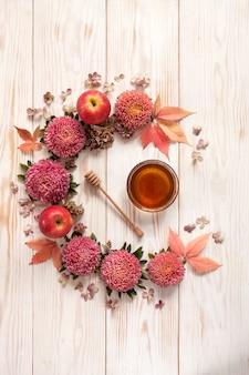 As maçãs, as flores cor-de-rosa e o mel com espaço da cópia formam uma decoração floral.