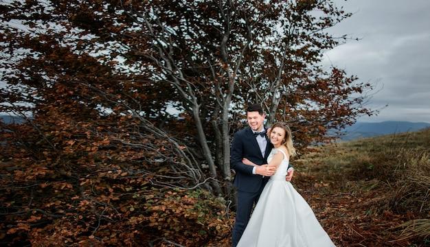 As mais felizes noivas abraçando perto de árvores