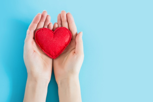 As mãos abertas da fêmea que guardam um coração vermelho em um fundo azul copiam o espaço para o texto. doação, conceito de assistência médica.