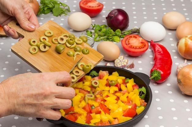 As mãos colocam azeitonas na frigideira de corte. legumes fatiados em uma panela.