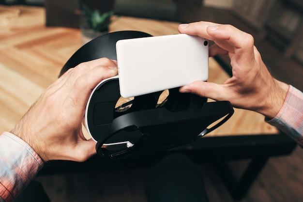 As mãos colocam o smartphone no fone de ouvido vr.