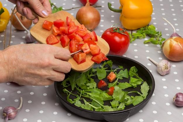 As mãos colocam tomates na tábua.
