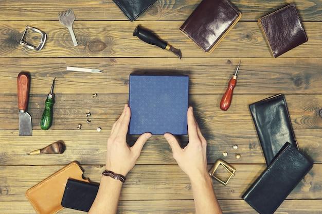 As mãos colocam uma nova carteira de couro em uma caixa de presente