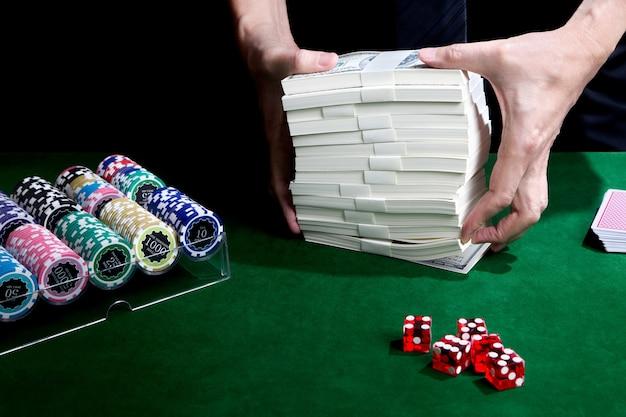As mãos colocando pilha de dólares na mesa verde