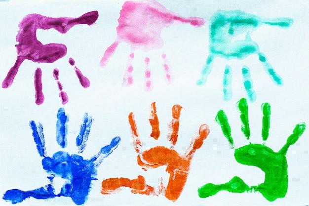 As mãos coloridas imprimem da aguarela.