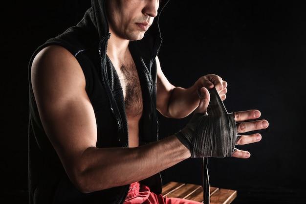 As mãos com bandagem de homem musculoso treinando kickboxing no preto