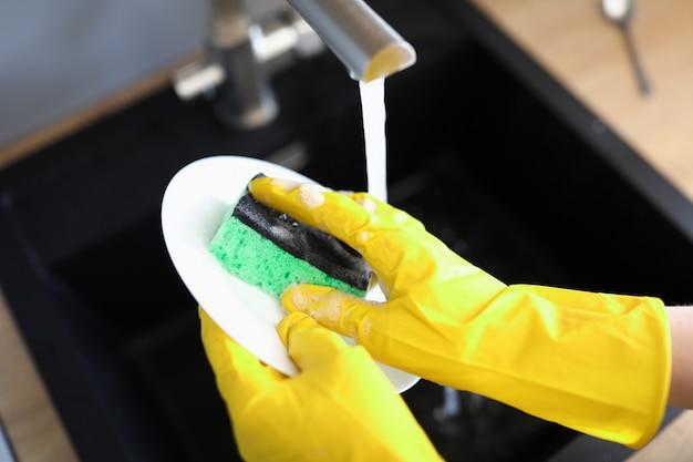 As mãos com luvas lavam a louça sob água de pressão