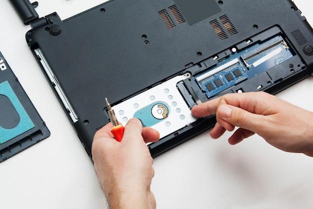 As mãos com uma chave de fenda desmontam a caixa do laptop em partes para substituir e reparar.