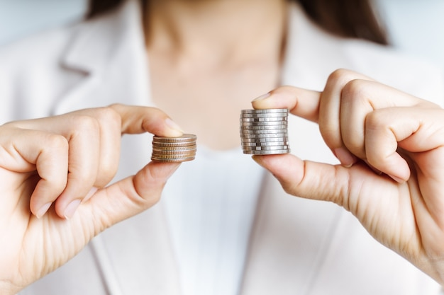As mãos comparam duas pilhas de moedas de tamanhos diferentes.