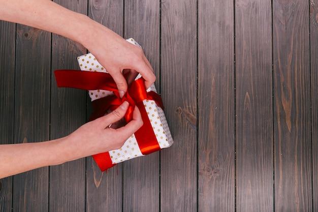 As mãos corrigem a gravata vermelha na caixa presente branca