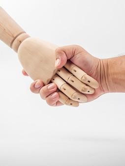As mãos da boneca de madeira estão segurando a mão humana em branco