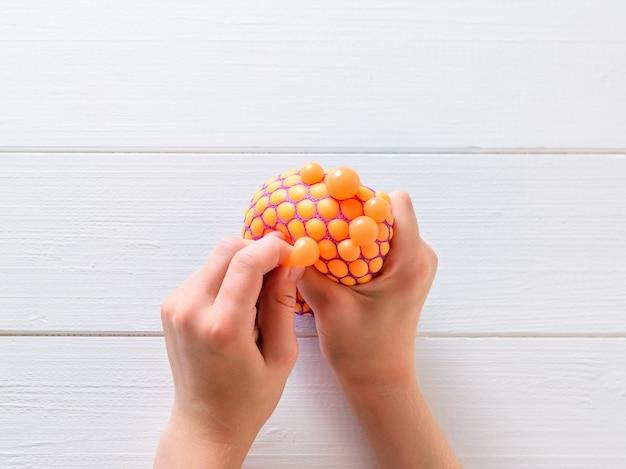 As mãos da criança amassam o brinquedo anti-stress sobre uma mesa branca. um dispositivo calmante. tratamento de transtornos mentais.