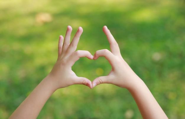 As mãos da criança com coração assinam no gramado do verde do borrão.