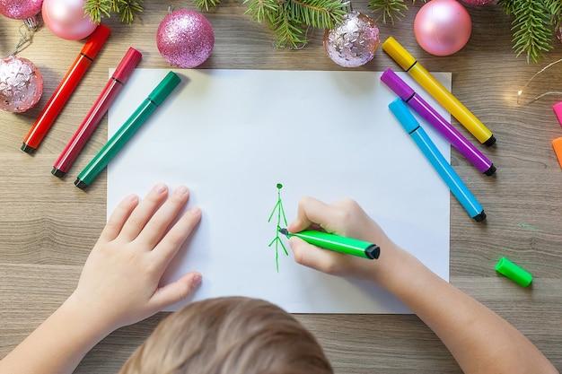 As mãos da criança desenham uma árvore de natal com marcadores no papel