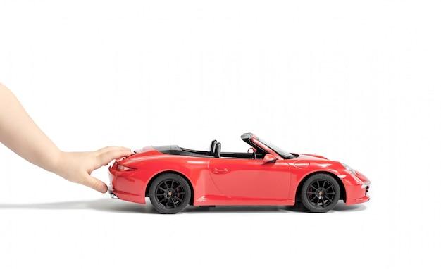 As mãos da criança empurrando o carro de brinquedo de coral porsche carrera s 911 modelo