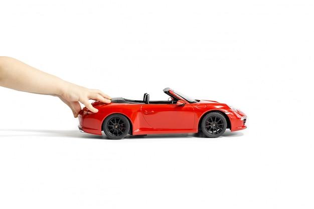 As mãos da criança empurrando o carro de brinquedo modelo porsche carrera s 911 vermelho