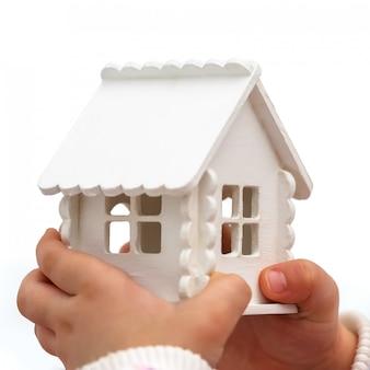 As mãos da criança está segurando uma casa de brinquedo em um branco