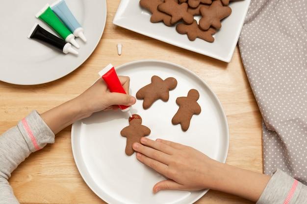 As mãos da criança que decoram cookies de um pão-de-espécie do natal usando o esmalte colorido, tabela de madeira, vista superior. biscoitos natalinos.
