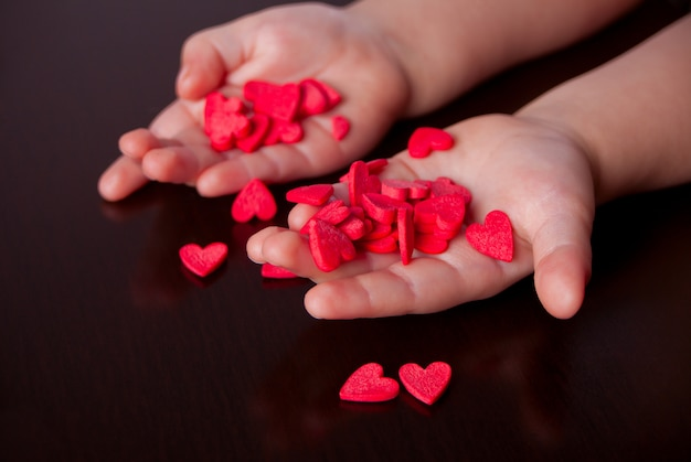 As mãos da criança que guardam corações vermelhos no fundo preto.