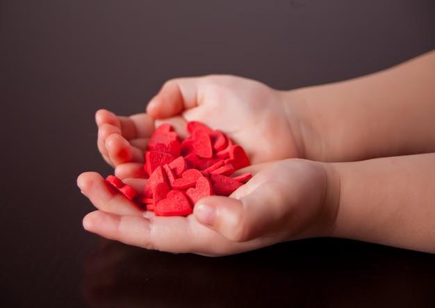 As mãos da criança segurando corações vermelhos sobre o fundo preto.