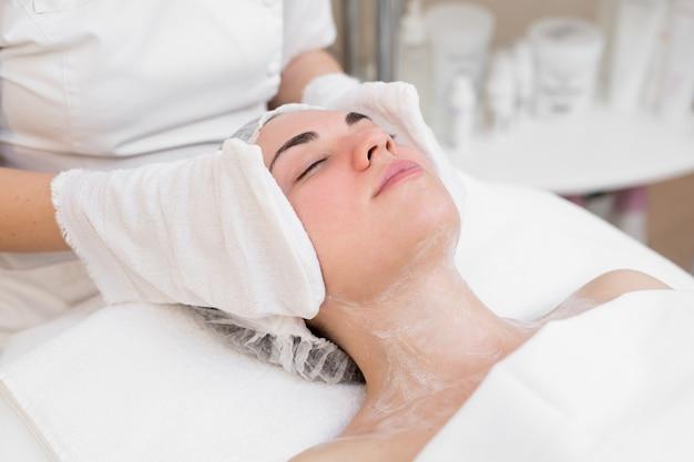 As mãos da esteticista limpam o rosto da garota no centro de cosmetologia com luvas brancas