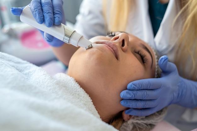 As mãos da esteticista usando dispositivo para limpeza ultrassônica, realizando procedimento de mulher na clínica de cosmetologia