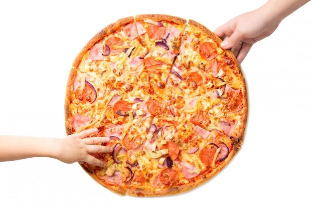 As mãos da fêmea e das crianças que tomam as fatias frescas e saborosos da pizza isoladas no branco.