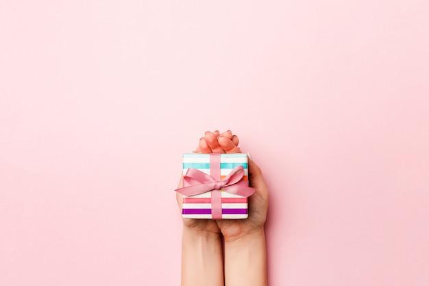 As mãos da fêmea segurando uma caixa de presente listrada com fita colorida na vida coral fundo. conceito de natal ou outra caixa de presente artesanal de férias, vista superior do conceito com espaço de cópia