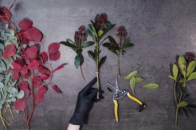 As mãos da florista e várias lindas flores estão sobre a mesa cinza.