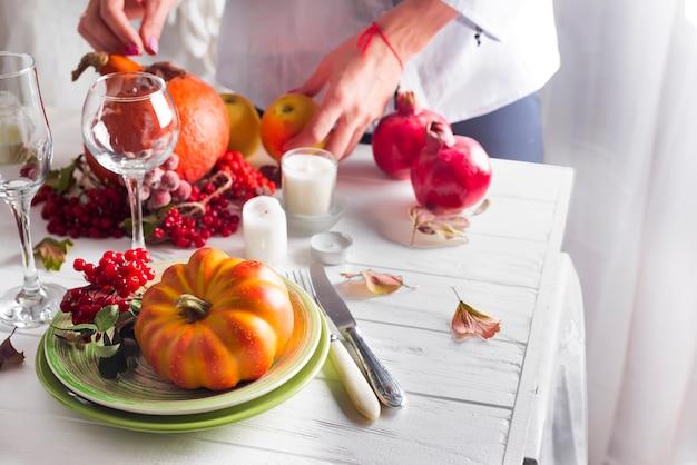 As mãos da garota preparar o cenário de mesa festiva de ação de graças
