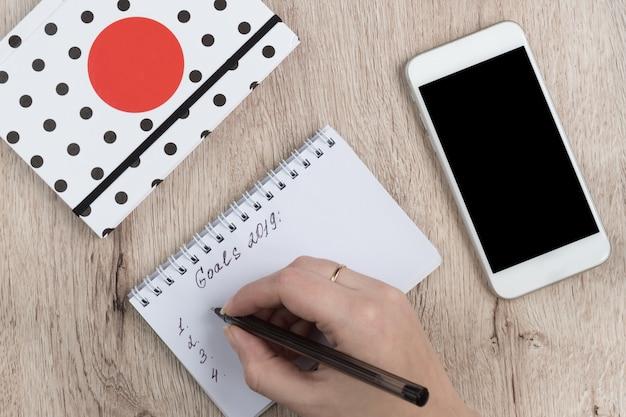 As mãos da jovem mulher guardam páginas abertas do caderno com caneta preta na tabela de madeira. lista de objetivos 2019.