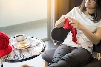 As mãos da jovem mulher que fazem malha camisolas mornas. Sentado na velha poltrona perto da janela
