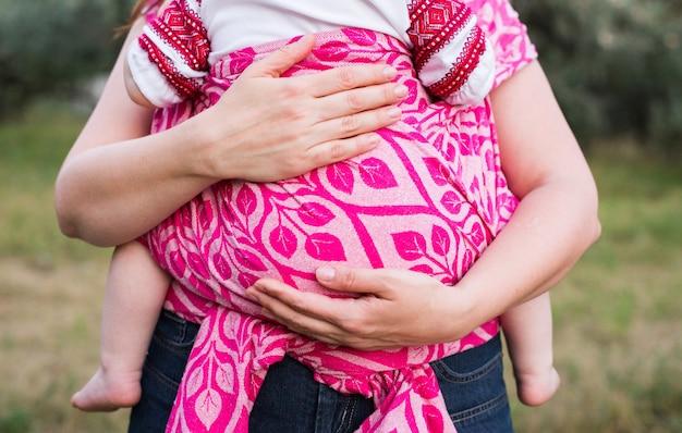 As mãos da mãe abraçam o bebê embrulhado em um porta-estilingue rosa ao ar livre