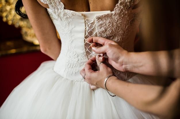 As mãos da mãe amarram o espartilho do vestido de casamento da noiva