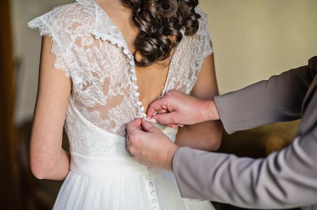 As mãos da mãe amarram o vestido da noiva
