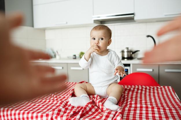 As mãos da mãe se estendendo para pegar um bebê fofo na mesa da cozinha