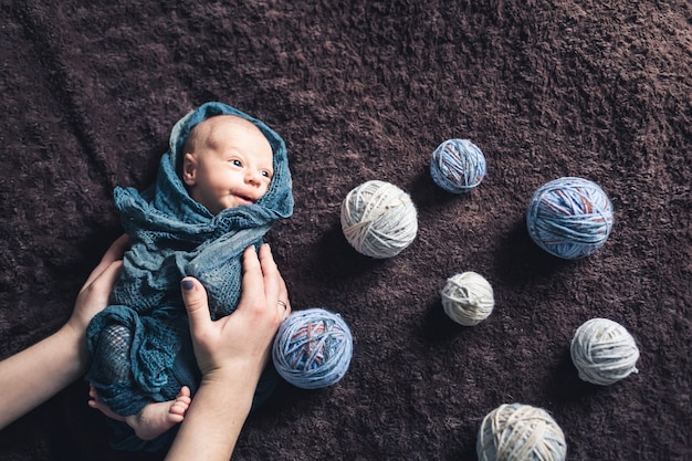 As mãos da mãe seguram o bebê enrolado em um cobertor entre emaranhados de linha