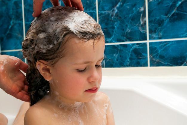 As mãos da mamãe lavando a cabeça da menininha no banheiro. o símbolo da educação em pureza e higiene.