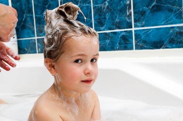 As mãos da mamãe lavando a cabeça da menininha no banheiro.