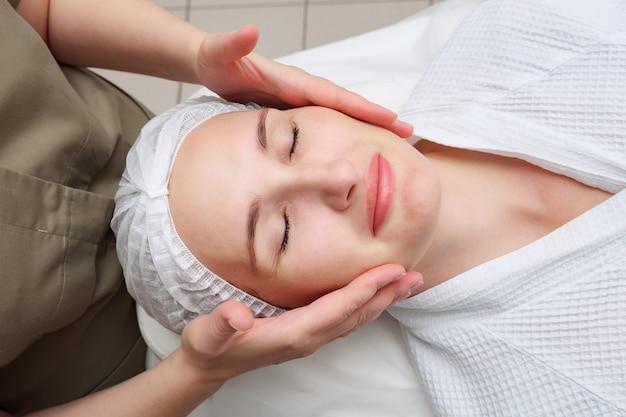 As mãos da massagista se movem fazendo uma massagem facial relaxante, vista superior